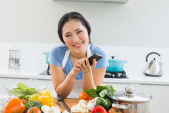 Smiling woman text messaging in front of vegetables in kitchen Royalty Free Stock Photo