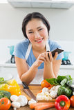 Smiling woman text messaging in front of vegetables in kitchen Royalty Free Stock Photography