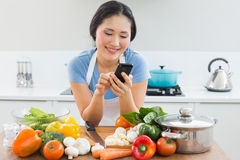 Smiling woman text messaging in front of vegetables in kitchen Stock Images
