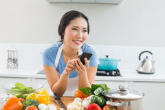 Smiling woman text messaging in front of vegetables in kitchen Royalty Free Stock Photos