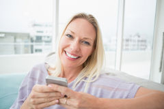 Smiling woman text messaging through mobile phone in living room Royalty Free Stock Photos