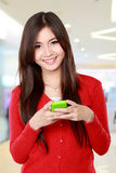 Smiling woman texting on cell phone Royalty Free Stock Image