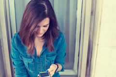 Smiling woman texting on her smart phone Royalty Free Stock Image