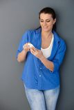 Smiling woman texting on mobile phone Royalty Free Stock Image
