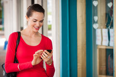 Smiling woman texting on mobile phone royalty free stock photos