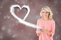 Smiling woman texting on mobile phone with digitally generated white heart Royalty Free Stock Photos
