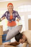 Smiling woman throwing pillow at man Stock Photography