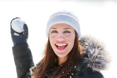 Smiling woman throwing snowball Stock Image