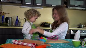 Smiling woman tie apron on little girl near kitchen table. Happy family time stock video