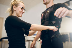 Smiling woman tightening belt on man ems suit Stock Photo