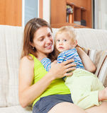 Smiling  woman with toddler on sofa Royalty Free Stock Photo
