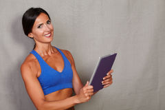Smiling woman with toothy smile holding tablet. And looking at camera against grey texture background Royalty Free Stock Photography