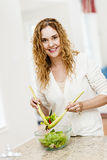 Smiling woman tossing salad in kitchen. Portrait of happy woman mixing salad in kitchen at home Stock Images