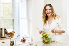 Smiling woman tossing salad in kitchen. Portrait of happy woman mixing salad in kitchen at home Royalty Free Stock Photo