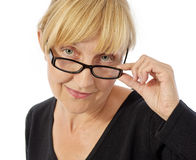Smiling woman touching her glasses Royalty Free Stock Image