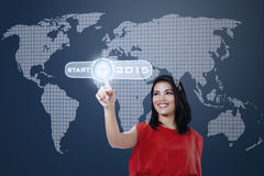 Smiling woman touching a start button. Young hispanic woman pushing a start button to future 2015 on a virtual screen Royalty Free Stock Images