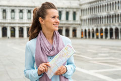 Smiling woman tourist holding map in empty St. Marks Square Stock Photography