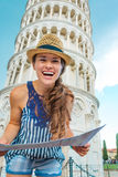 Smiling woman tourist holding map in front of Tower of Pisa. A happy woman tourist wearing a hat is holding a map and laughing. Behind her, the Leaning Tower of Royalty Free Stock Images