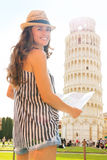 Smiling woman tourist holding map at Leaning Tower of Pisa Royalty Free Stock Image