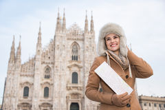 Smiling woman tourist with map in the front of Duomo, Milan Royalty Free Stock Images