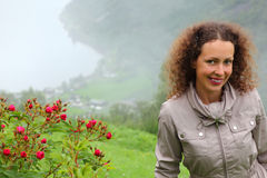 Smiling woman tourist stands near mountain Royalty Free Stock Images