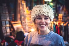 Smiling woman tourist trying on traditional Balkan hat on local souvenir market during her travel holidays Stock Images