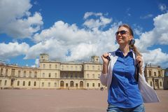 A smiling woman tourist walking in the city. A female tourist on the street in front of the ancient architecture. royalty free stock image