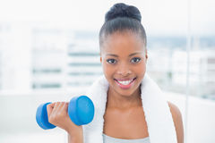 Smiling woman with towel around her neck working out with dumbbell Stock Photo