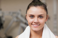 Smiling woman with towel around neck in gym Stock Photo
