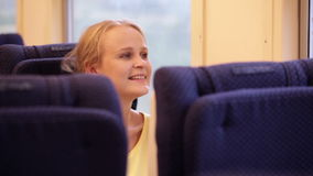 Smiling woman in the train. Happy young woman traveling by train and looking out the window stock video