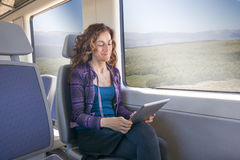 Smiling woman in train reading digital tablet Royalty Free Stock Image
