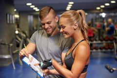 Smiling woman with trainer and clipboard in gym Royalty Free Stock Photos