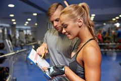 Smiling woman with trainer and clipboard in gym Stock Photography