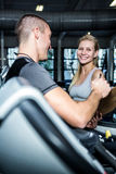 Smiling woman with trainer using treadmill Royalty Free Stock Photos