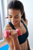 Smiling woman training with dumbbells Stock Photography