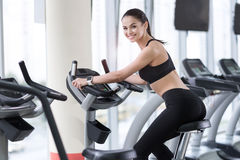 Smiling woman training on an exercise bike Royalty Free Stock Image