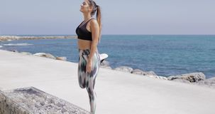 Smiling woman training on shore of resort. Pretty sportive girl posing on background of blue ocean working out on waterfront of resort and smiling in tropical stock video footage