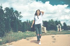 Smiling woman traveler with a backpack on her back walking. On an unfamiliar street during summer adventure. Happy teenager girl walking Royalty Free Stock Photos