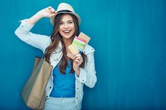 Smiling woman traveler holding passport with ticket. Smiling woman traveler holding passport with ticket and credit card. Blue wall back Stock Image
