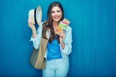 Smiling woman traveler holding passport with ticket. Smiling woman traveler holding passport with ticket and credit card. Blue wall back Royalty Free Stock Images