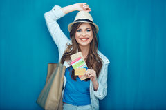 Smiling woman traveler holding passport with ticket. Smiling woman traveler holding passport with ticket and credit card. Blue wall back Royalty Free Stock Photo