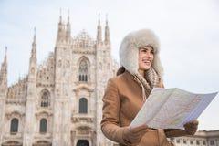 Smiling woman traveler with map looking aside near Duomo, Milan Royalty Free Stock Image