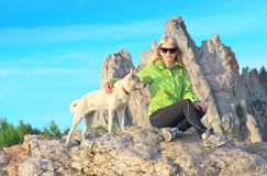 Smiling Woman Traveler and white dog sitting on stones relaxing with Rocky Mountain Royalty Free Stock Photography