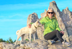 Smiling Woman Traveler and white dog sitting on stones relaxing with Rocky Mountain peak Royalty Free Stock Photos