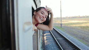 Smiling woman traveling by train. Smiling young woman traveling by train looking out though open window stock video