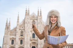 Smiling woman traveller with map pointing on Duomo, Milan Royalty Free Stock Image