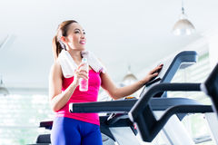 Smiling woman on treadmill presenting water bottle Royalty Free Stock Photos