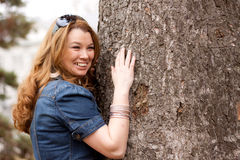 A smiling woman by a tree Royalty Free Stock Images