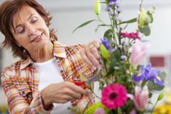 Smiling woman trimming flowers in floral arrangement in classroom Royalty Free Stock Photography