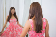 Smiling woman trying on a dress. At a boutique royalty free stock photography